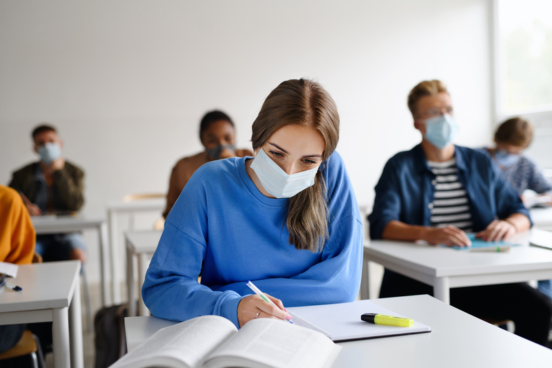 female student in mask at desk